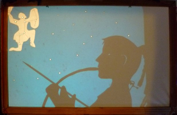 Orion constellation on blue transparency with puppet of Artemis watching it