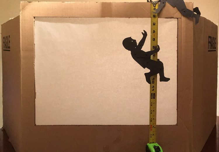 shadow puppets measuring a cardboard box theater