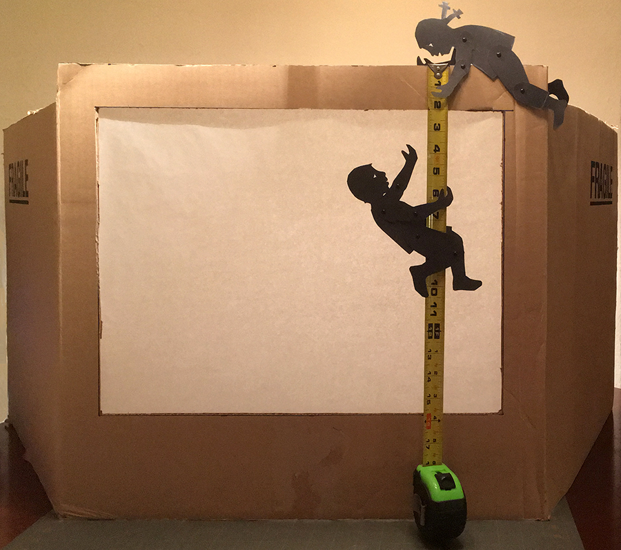 boy and girl shadow puppet climbing a measuring tape to make a cardboard box theater
