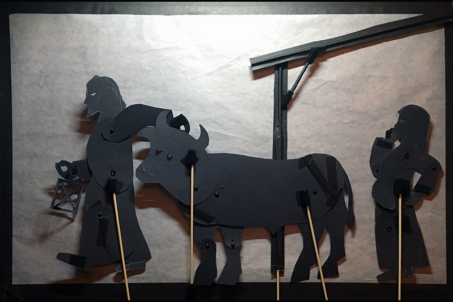 Shadow puppets of Joseph taking the oxen out off the manger while Mary watches