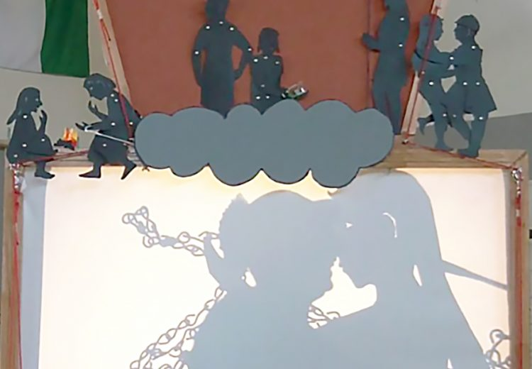 Shadow puppet screen showing a man kissing a life size puppet, project from an overhead project.