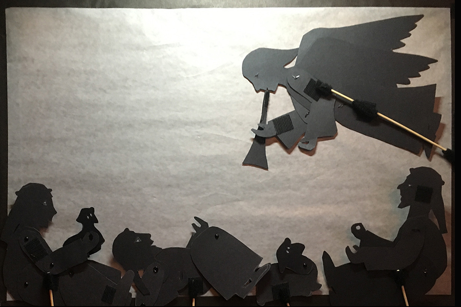 Shadow puppets of angel waking up the shepherds to tell the news about Jesus' bir