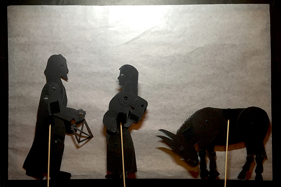 Shadow puppets of Joseph, Mary, and the donkey, with Mary stretching her back