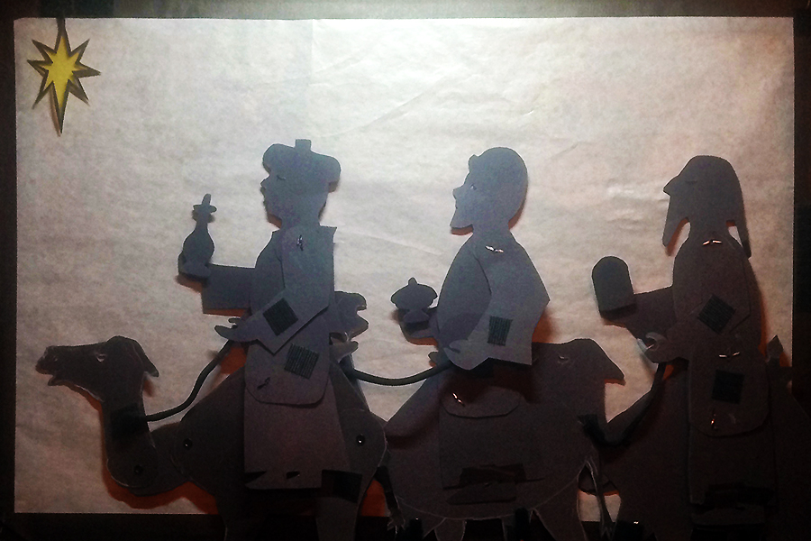 Shadow puppets of three wise men on camels following the star