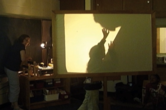 Screen showing child pushing up a boulder projected from overhead projector