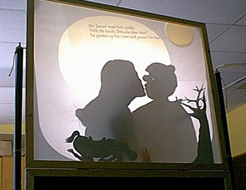 Shadow screen showing a teacher kissing a puppet knight projected from overhead projector