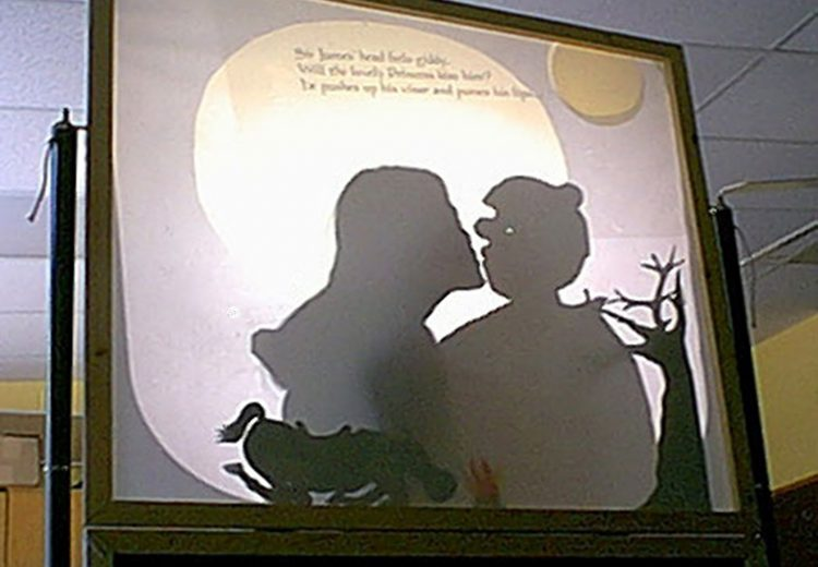 Teacher kissing a puppet of a knight, projected from an overhead projector