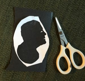 Demonstration how to cut out a silhouette by taping it to poster board