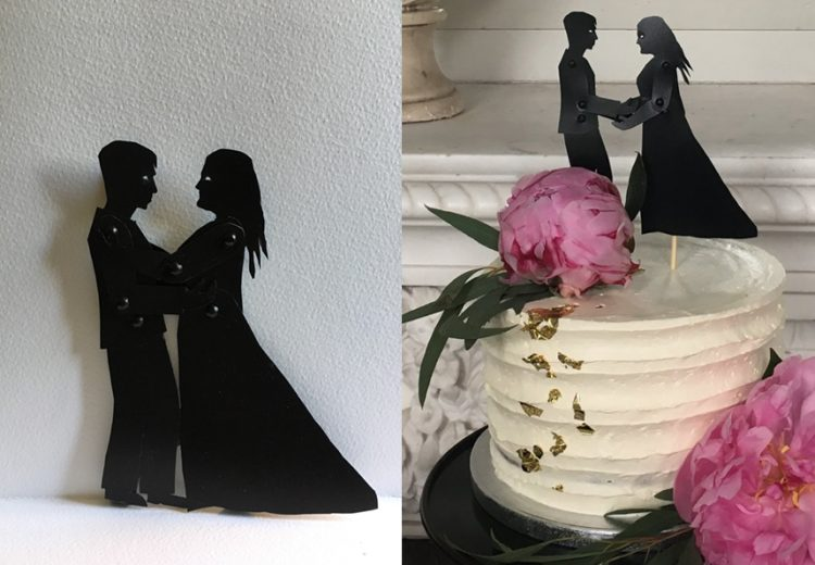 Small shadow puppets holding hands and embracing with wedding cake