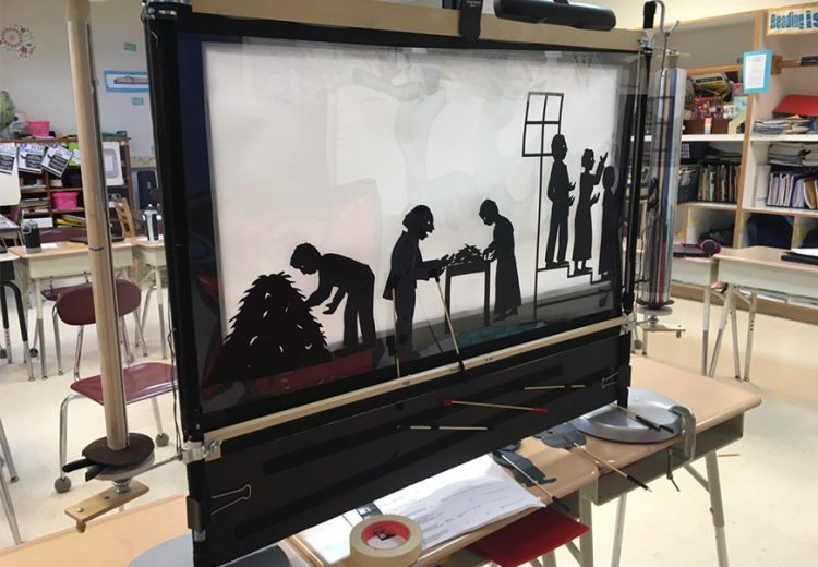 "Back of a shadow puppetry screen with scrolling transparent film depicting the opening scenes of the story of Henry ""Box"" Brown"