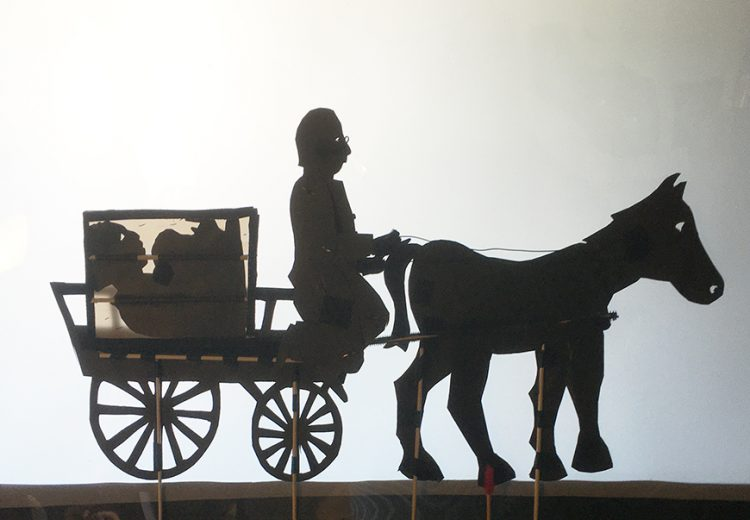 shadow puppets of man riding a horse and wagon
