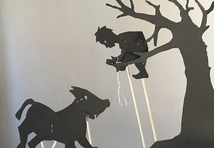 Silhouettes of Peter in a tree trying to catch the wolf with a rope