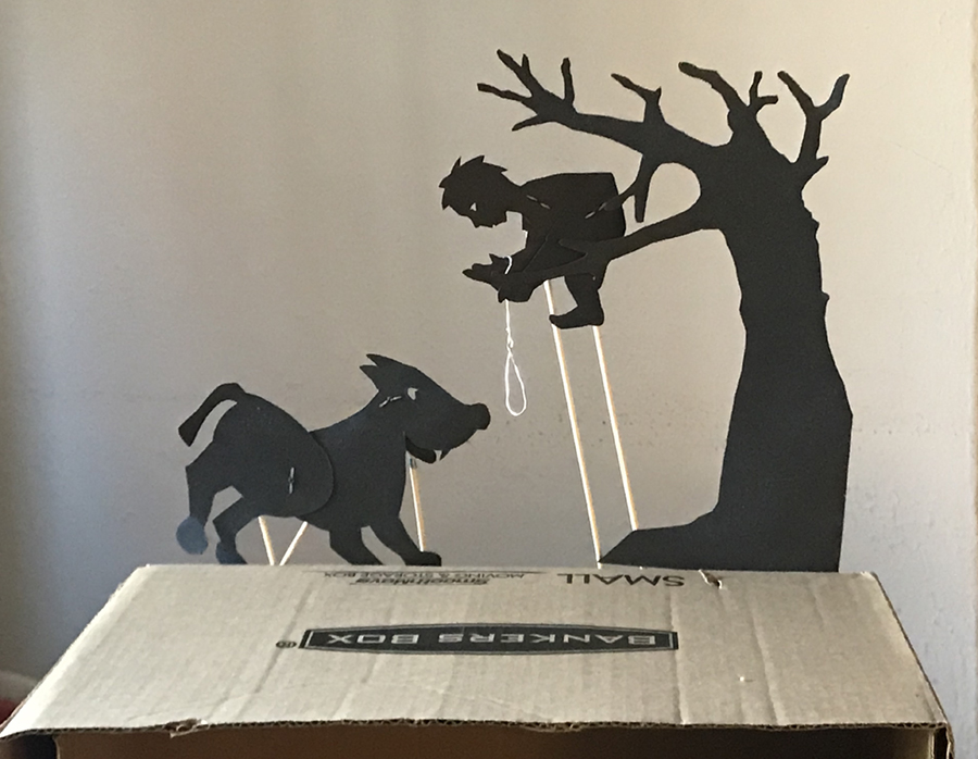 Silhouette puppets of Pet in a tree holding a rope with wolf with rods stuck in the bottom side of a box