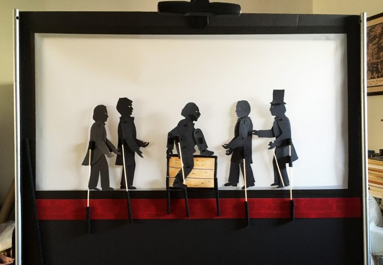 Inside of a shadow puppetry screen with puppets from the story of Henry Box Brown