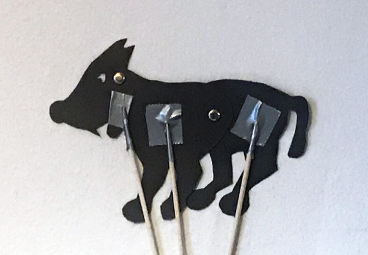Silhouette puppet of a wolf with movable jaw, front and back