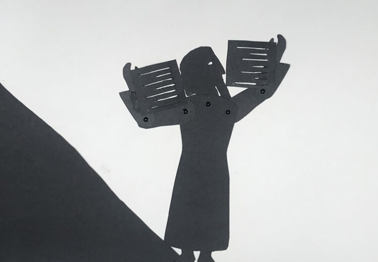 shadow puppet of bearded old man holding two annotated tablets above his head